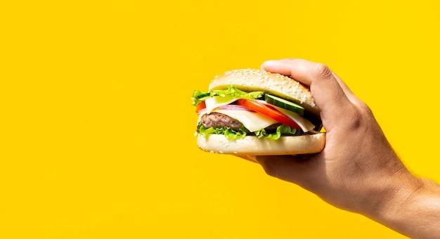黄色の背景の前で開催されたハンバーガー