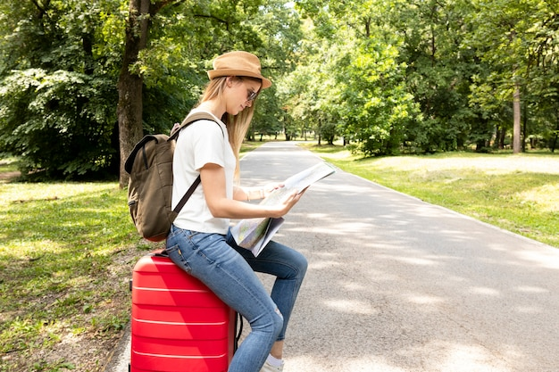 Женщина смотрит на карту в парке