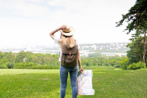 地図を持つ女性は彼女の帽子を保持しています。