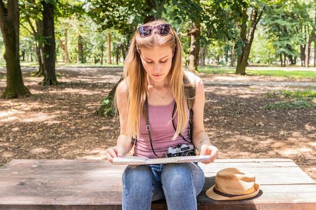 ベンチに座って地図を見る女性