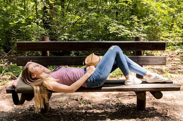 ベンチに横になって空を見ている旅行者