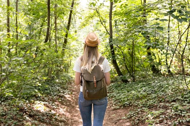 Женщина гуляет в лесу сзади