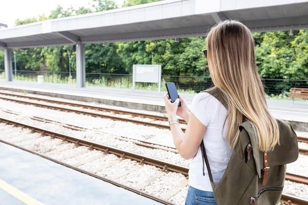 Женщина смотрит на телефон сзади