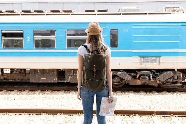 通過する列車を後ろから見ている女性