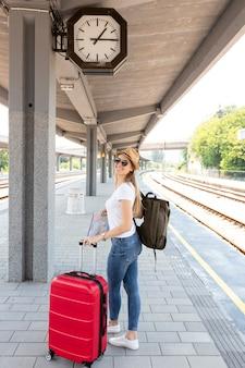 駅で彼女の荷物を持つ少女