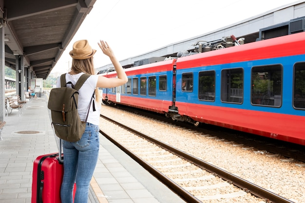 後ろから電車で手を振っている女性