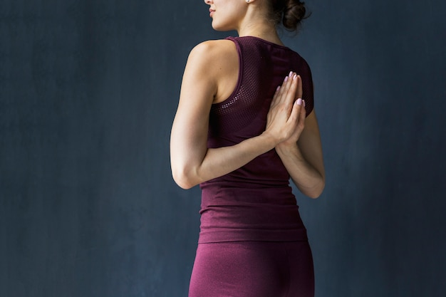 彼女の背中の後ろに祈る位置で手を繋いでいる女性