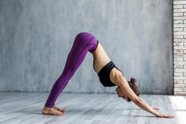 Женщина, стоящая в позе йоги собаки, обращенной вниз