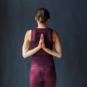 祈りの位置で彼女の背中の後ろに手を握って女性