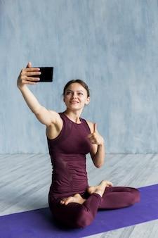Радостная женщина фотографирует на занятиях йогой