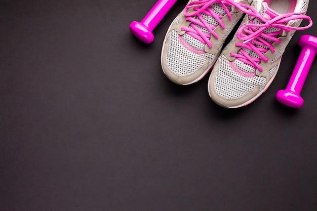 ピンクの靴とダンベルのトップビューの配置