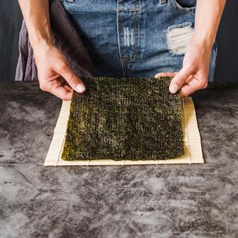 Руки держат нори на столе для приготовления пищи