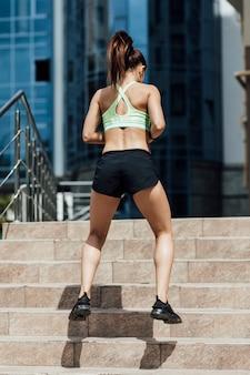 階段でジャンプ女性の背面図