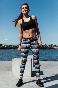 バックグラウンドで湖と運動の女性