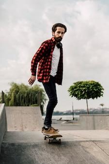 スケートパークでスケートボードの男
