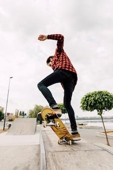 公園でスケートボードのトリックをしている男