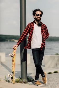 スケートボードを持って笑みを浮かべて男