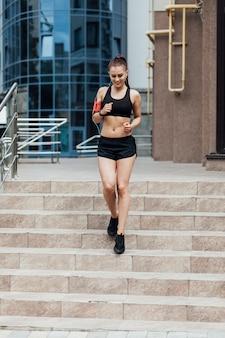 階段でジョギングの女性の正面図