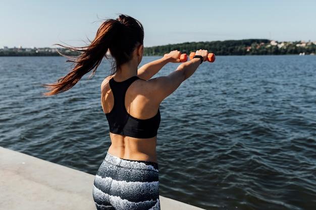 女性の重みでトレーニングの背面図