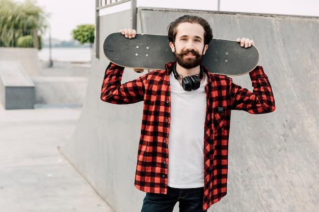 スケートボードを保持しているスケートパークの男
