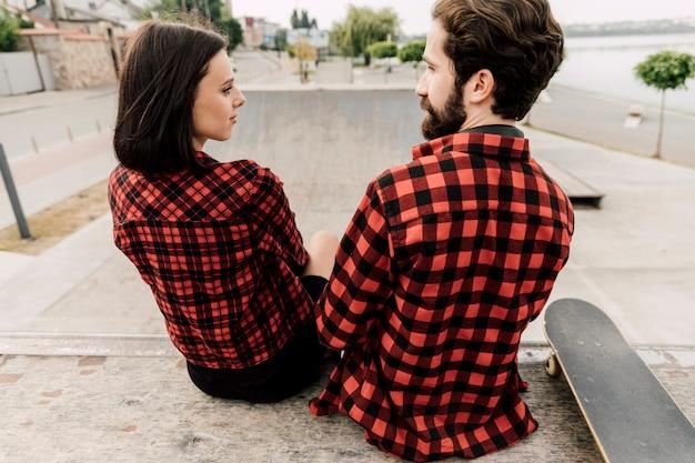 お互いを見ているカップルの背面図