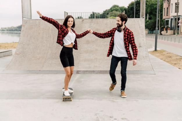 スケートボードに乗るガールフレンドを助ける男