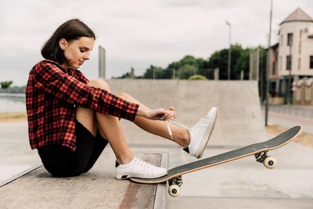 Вид сбоку женщины, связывая ее шнурки