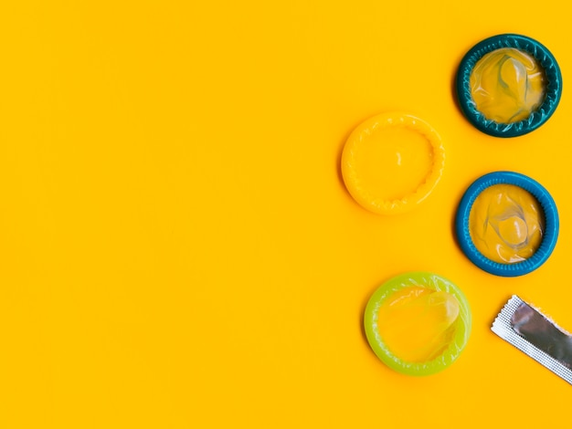 Плоские лежали разноцветные презервативы на желтом фоне