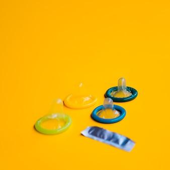 Высокий угол развернутых презервативов на желтом фоне