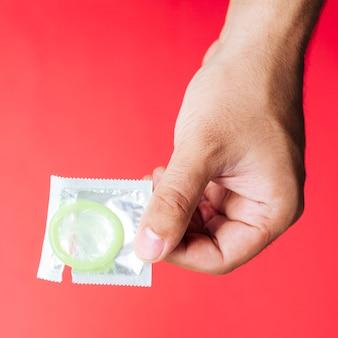 Рука крупным планом держит презерватив с красным фоном