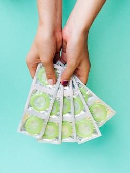 Макро руки держат завернутые зеленые презервативы