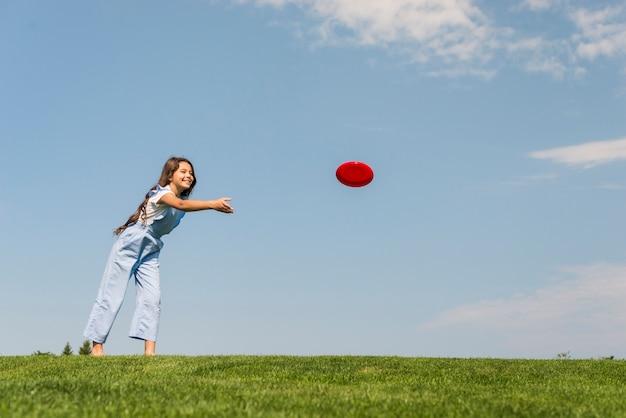 Длинный выстрел маленькая девочка играет с красным фрисби