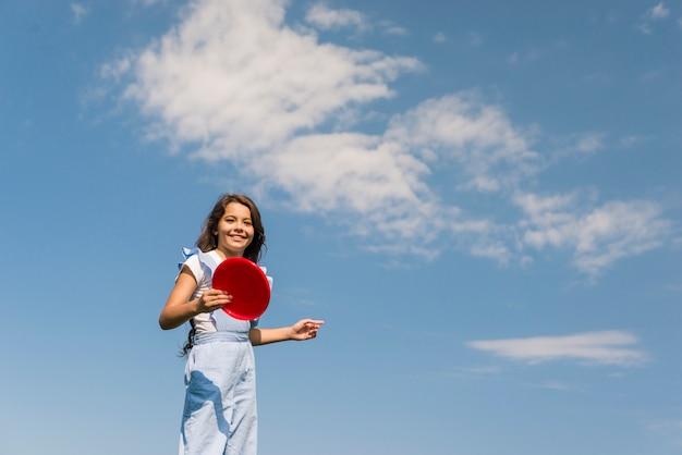 Вид спереди маленькая девочка, играя с красной фрисби