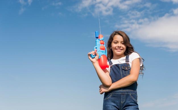 Маленькая девочка позирует с водяной пушкой