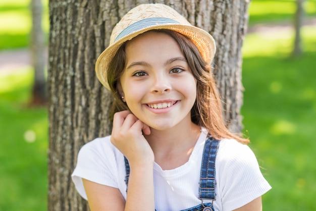 木の前でポーズをとってスマイリー少女