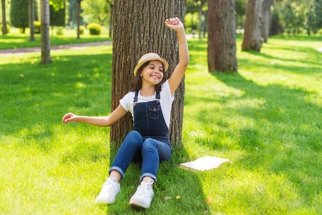 木の前でポーズをとってロングショットの女の子