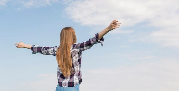 青い空を楽しんでいる背面図女の子