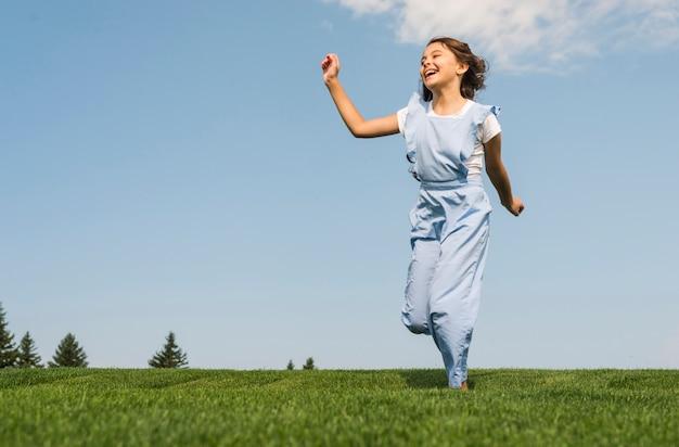Веселая маленькая девочка работает на траве