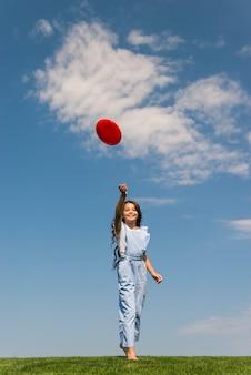 赤いフリスビーで遊ぶ女の子の正面図