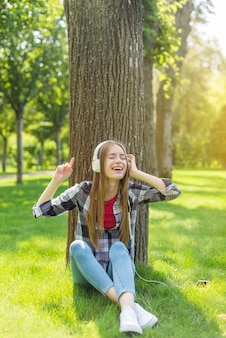 白いヘッドフォンで音楽を聴いている女の子