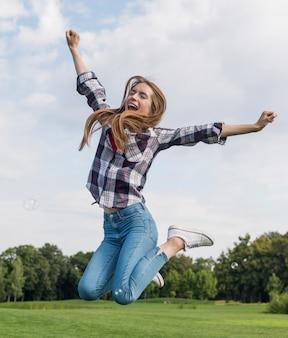 屋外ジャンプかわいいブロンドの女の子