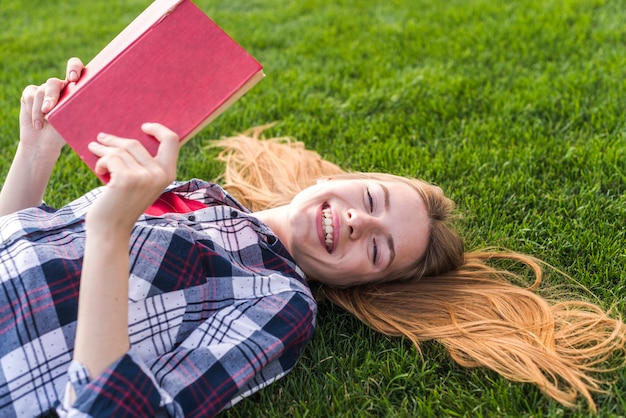 Девушка высокого угла читая книгу на траве