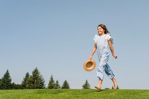 草の上を裸足で歩く女の子