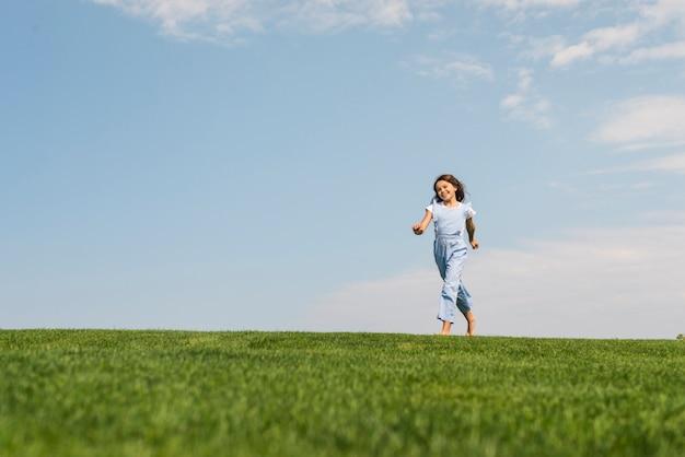 草の上を裸足で走っている少女