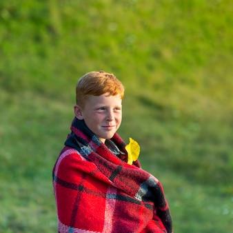 毛布で覆われているかわいい若い男の子