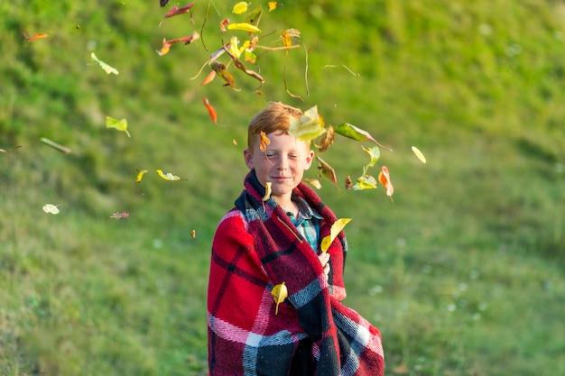Рыжий мальчик играет с листьями