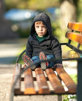 木製のベンチに座っているパーカーの少年