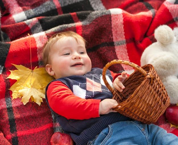 Очаровательны рыжий ребенок держит корзину