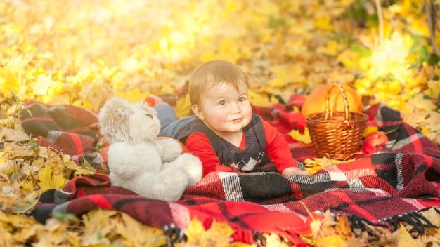 Милый маленький мальчик с мишкой, сидя на одеяле