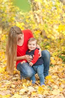 葉に囲まれた幼い息子を保持しているお母さん